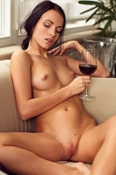 A sexy brunette babe with a hot body enjoying a glass of wine