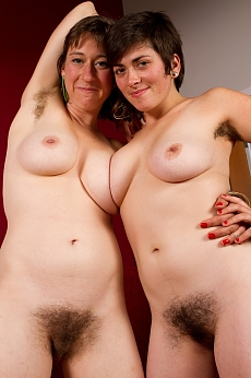 Charlie and Louise smile as they kiss each others necks and rub the fluffy hairy pussy together on the sofa