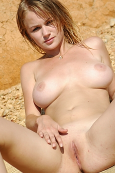 Sweet blonde gets naked and plays up on the beach