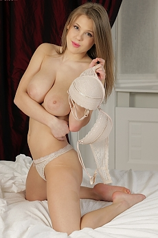 A horny girl with big breasts fingering her tight pussy on her bed