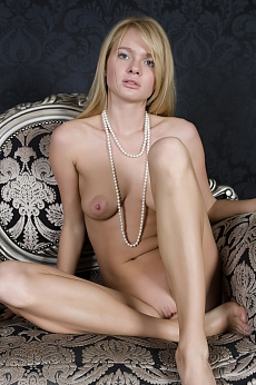 a blonde girl posing naked in a chair